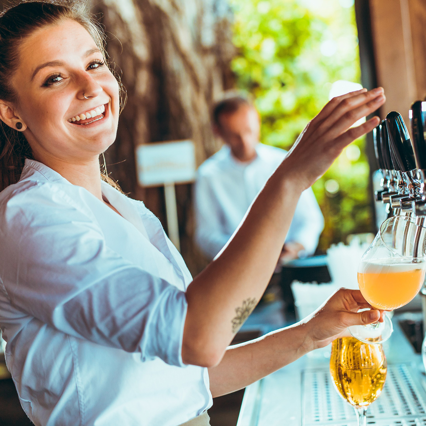 Waitress pouring beer at the Alte Kaisermühle in Vienna next to the Alte Donau
